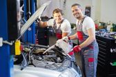 Two mechanics adding oil level in a car workshop — 图库照片