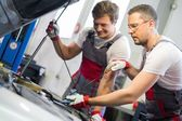 Two mechanics checking oil level in a car workshop — ストック写真