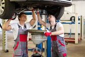 Two mechanics changing oil  in a car workshop — Stock Photo