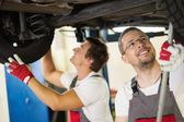 Servicemans checking suspension in a car workshop — Stock Photo