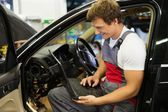 Serviceman making car diagnostics with laptop in a workshop — Stock Photo