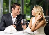 Cheerful couple in a restaurant with glasses of red wine — Stok fotoğraf