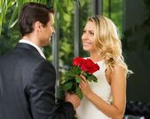 Handsome man with bunch of red dating his lady — Stock Photo