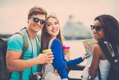 Multi-ethnic friends tourists with map and coffee cups near river in a city — ストック写真