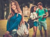 Beautiful young girl student in a city park on summer day  — 图库照片