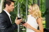 Cheerful couple with glasses of red wine talking — Stock Photo