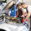 Two mechanics fixing car in a workshop — Stock Photo #48794791