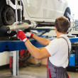 Young serviceman checking wheel alignment in a car workshop — Stock Photo #48794793