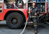 Firefighter near truck with equipment with water water hose over shoulder  — Stock Photo