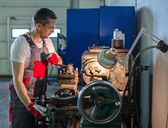 Serviceman working on lathe machine in car workshop — Stock Photo