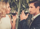 Couple with glasses of red wine in restaurant — Stock Photo