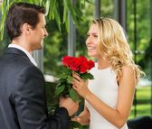 Handsome man with bunch of red roses dating his lady — Stock Photo