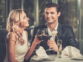 Cheerful couple in a restaurant with glasses of red wine — Stock Photo