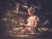 Blond retro woman with a book in summer dress sitting on a meadow — Stock Photo