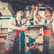 Two mechanics changing oil  in a car workshop — Stock Photo #49193413