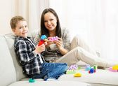 Happy young mother with her son on a sofa playing with building kit — Stock Photo