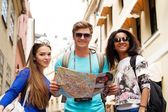 Multi ethnic friends tourists with map in old city  — Stock Photo