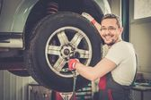 Ruota svitando serviceman allegro in officina auto — Foto Stock
