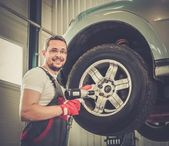 Cheerful serviceman unscrewing wheel in car workshop  — Stock Photo