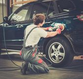 Serviceman polishing car body with machine  in a workshop — Stock Photo