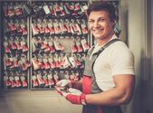 Cheerful serviceman near stand with colour samples in car body workshop — Stock Photo