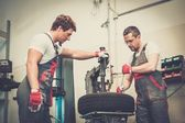 Two mechanics changing tire on a wheel in a car workshop — Stock Photo