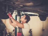 Serviceman checking suspension in a car workshop  — Stock Photo