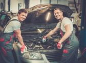 Two mechanics fixing car in a workshop — Stock Photo