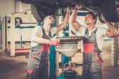 Iki mekanik bir araba atölye yağ değiştirme — Stok fotoğraf