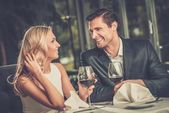 Cheerful couple in a restaurant with glasses of red wine — Foto Stock