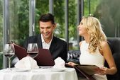 Cheerful couple with menu in a restaurant  — Foto Stock