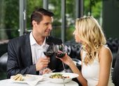 Cheerful couple in a restaurant with glasses of red wine — Photo