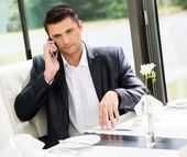 Handsome businessman talking over mobile phone in restaurant — Stock Photo