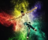 Man dancer showing break-dancing moves against colourful powder explosion — Stock Photo