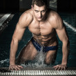 Young muscular swimmer in a swimming pool — Stock Photo #49626313
