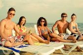 Group of multi ethnic friends sunbathing on a deck chairs on a beach  — Стоковое фото