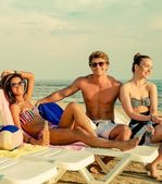 Group of multi ethnic friends sunbathing on a deck chairs on a beach  — ストック写真