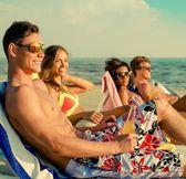 Group of multi ethnic friends sunbathing on a deck chairs on a beach  — Stock Photo