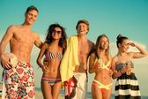 Group of multi ethnic friends walking on a beach — Foto Stock