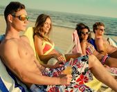 Group of multi ethnic friends sunbathing on a deck chairs on a beach  — Stock fotografie