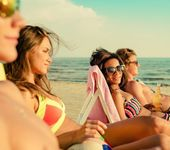 Group of multi ethnic friends sunbathing on a deck chairs on a beach  — Stok fotoğraf