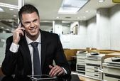 Handsome man in black suit with mobile phone and tablet pc in modern office  — Stock Photo