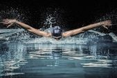 Young man in swimming cap and goggles swim using breaststroke technique — Stock Photo