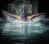 Ung man i simning cap och glasögon simma med bröstsim teknik — Stockfoto