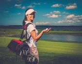 Woman with bag and ball on a golf field — Stock Photo