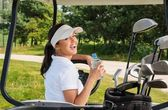 Woman with bottle of water driving golf cart — Stock Photo