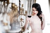 Woman with glass of red wine near fireplace — Stock Photo