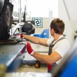 Young serviceman checking wheel alignment in a car workshop — Stock Photo #50513519