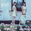 Tow women in dress near luxury building facade among roses  — Stock Photo #50513657