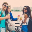 Multi-ethnic friends tourists with map and coffee cups near river in a city — Stock Photo #50513867